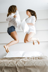 Two beautiful women jumping from joy on bed