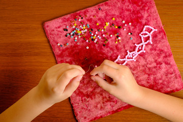 Kid's hands collect pink beads on a drawstring