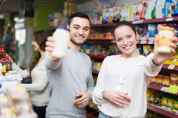 Smiling people choosing tinned food