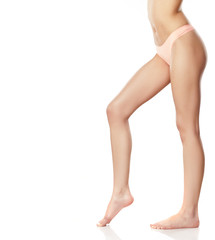 naked female legs and pink panties on a white background