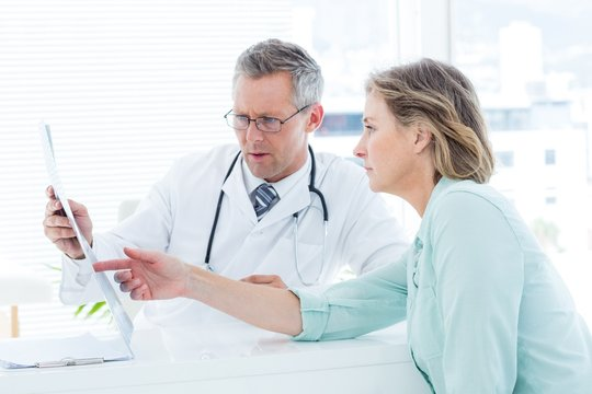 Doctor having conversation with his patient and holding xray