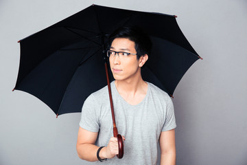 Asian man standing with umbrella and looking away