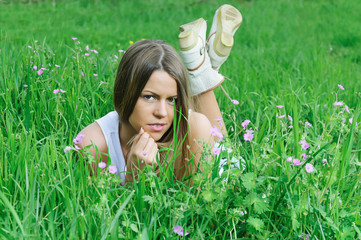 Cheerful young woman lying in the nature