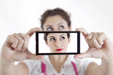 pretty woman taking a selfie using her smartphone