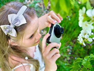 Girl photographs blossoming tree.