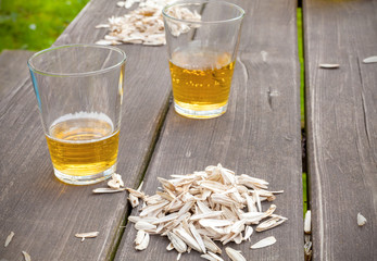 Sunflower seed husks and two glasses on the garden table.