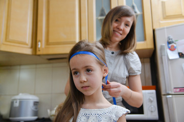 Mom makes daughter hairstyle