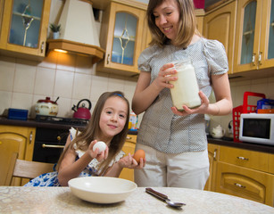 Making breakfest. Mom teach daughter to cook