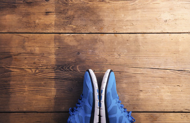 Pair of blue running shoes laid on a wooden floor background