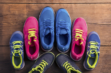 Four pairs of various running shoes laid on a wooden background