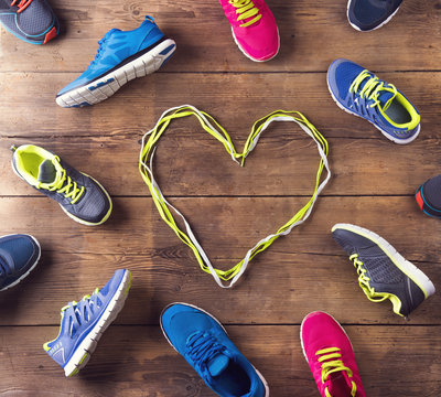 Various running shoes land shoelaces heart on wooden background