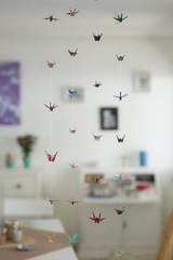 Origami Kraniche schweben im Raum