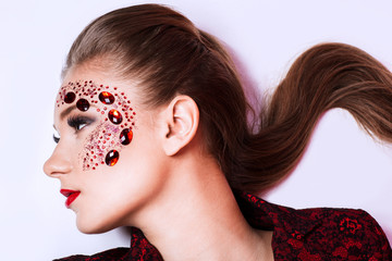 creative fashion girl with red stones on the face
