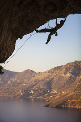 Male rock climber on overhanging cliff, Kalymnos Island, Greece