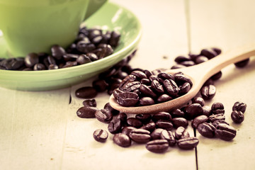 roasted coffee beans in wooden spoon on green cup background in
