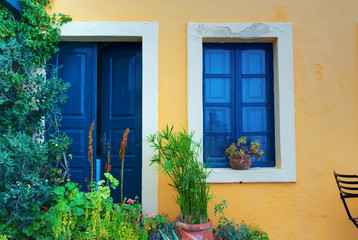 Old house yellow wall with blue door and window. Greece Santorin