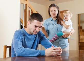 Family quarrel. Sad man against wife with baby