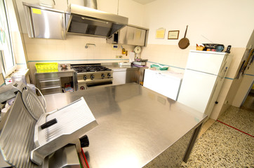 stainless steel kitchen with gas stove and an industrial meat sl