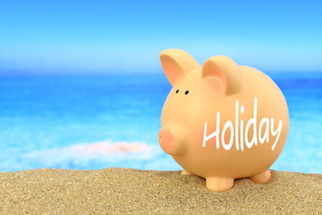 Word Holiday written on piggy bank on the beach