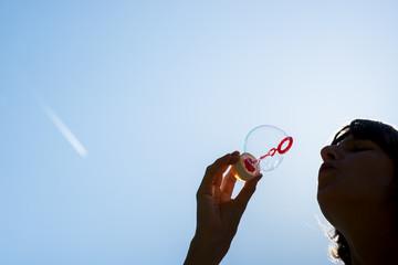 Woman blowing bubbles against a blue sky