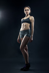 Portrait of sporty young woman with muscular body looking at cam