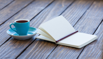 Cup of coffee and notebook with pencil
