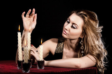 Beautiful young woman near the candles