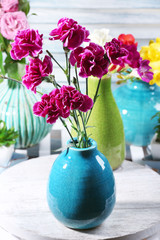 Different beautiful flowers in vases on table close up
