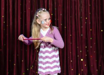 Smiling little blond girl wearing pantomime makeup