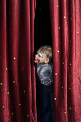 Boy Dressed Up as Clown Peeking Thru Stage Curtain