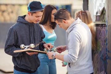 Two teenage boys talking about their skateboard