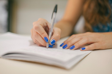 Closeup of a Woman Hand Writing in a Diary