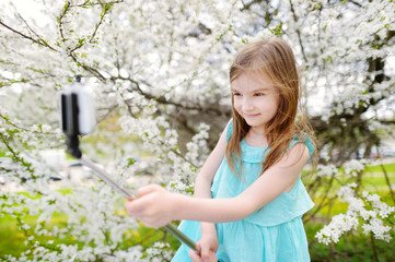 Adorable little girl taking a photo of herself