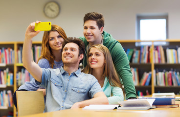 students with smartphone taking selfie in library