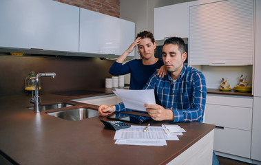 Unemployed young couple with debts reviewing their bank accounts