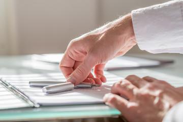 Businessman reaching for his fountain pen