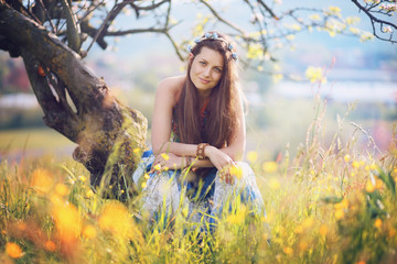 Smiling gypsy woman posing among flowers