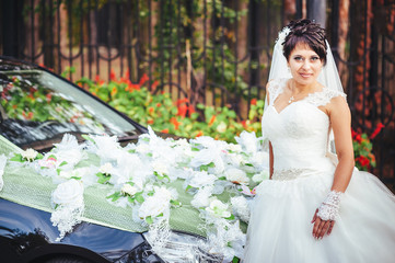 The bride near a black wedding car