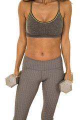woman in gray fitness outfit body hold weights