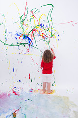 Young Little Kid Painting on White Big Wall