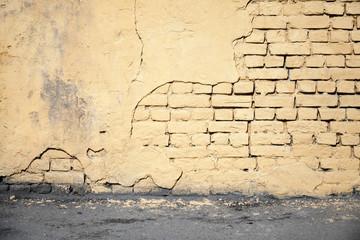 Wall Mural - Yellow damaged brick wall and asphalt