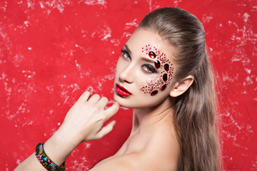 creative fashion girl with red stones on the face, hair