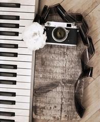 Artwork in retro style, old camera, film, piano, white flower