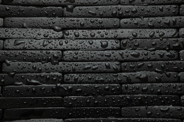 Black tile background with water