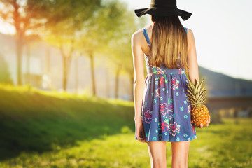 Young woman in floral dress and fedora hat holding pineapple