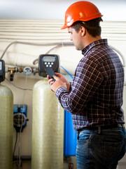 engineer taking meter readings from industrial pumps at factory