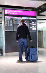 Man with suitcase looking at flight connections information.