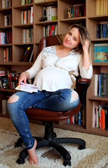 Young pregnant woman sitting on a chair.