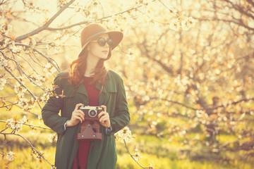 women with camera in blossom apple tree garden