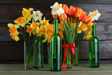 Daffodils and tulips in a glass vase on a wooden background